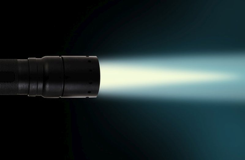 LED flashlight beam on black background